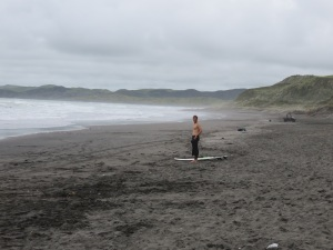 Hot surfer on the black sand beach in Raglan.